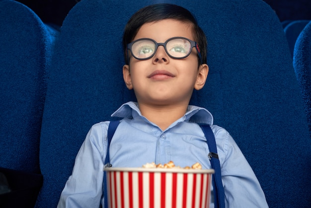 Garoto com balde de pipoca assistindo desenho animado no cinema.
