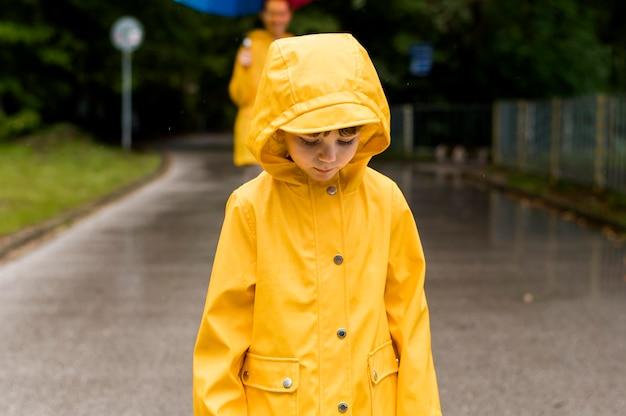 Garoto com capa de chuva, olhando para baixo