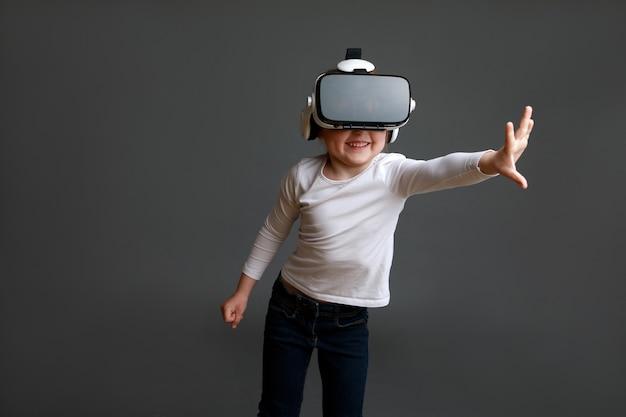 Garoto com fone de ouvido de realidade virtual, tiro isolado na superfície cinza. criança explorando o mundo virtual digital com óculos de realidade virtual.