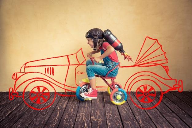Garoto com jet pack andando de bicicleta. criança brincando em casa. conceito de sucesso, líder e vencedor