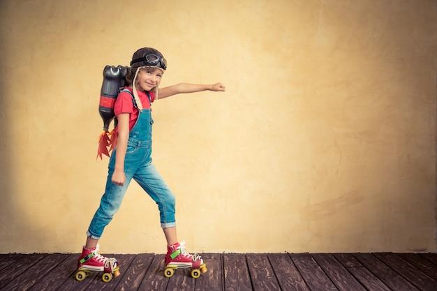 Garoto com jet pack andando de patins. criança brincando em casa. conceito de sucesso, líder e vencedor