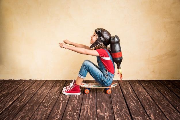 Garoto com jet pack andando de skate. criança brincando em casa. conceito de sucesso, líder e vencedor