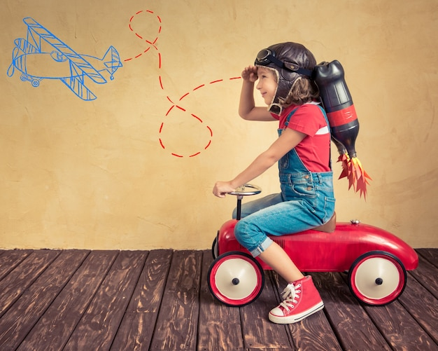 Garoto com jet pack dirigindo um carro de brinquedo retrô. criança brincando em casa. conceito de sucesso, líder e vencedor