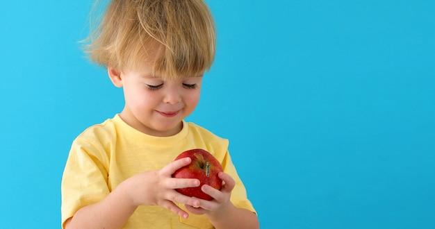 Garoto com maçã vermelha deliciosa em background azul