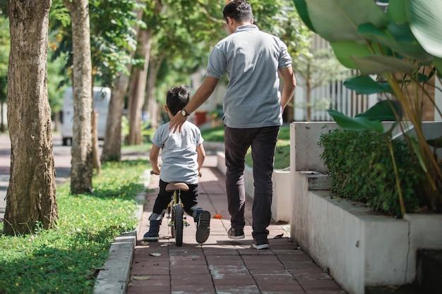 Garoto com seu pai aprendendo a andar de bicicleta