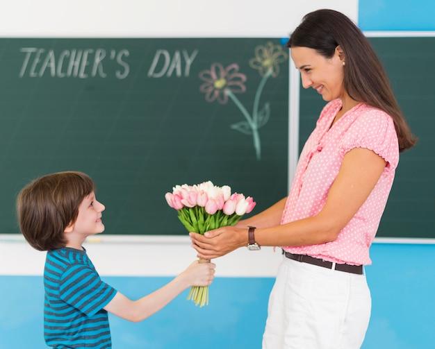 Garoto com vista lateral dando um buquê de flores para a professora