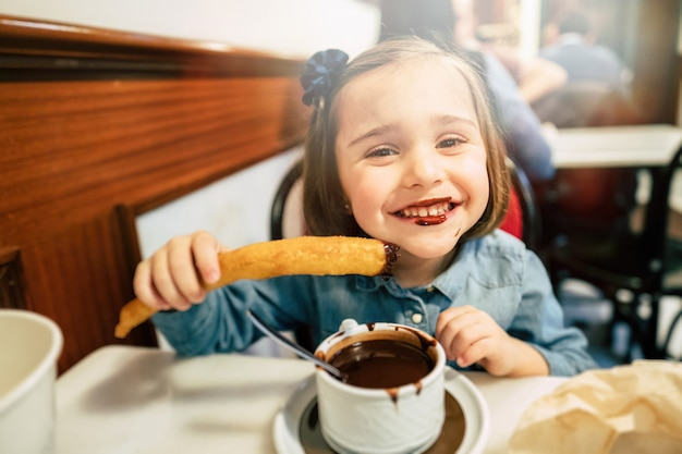 Garoto comendo churros e chocolate