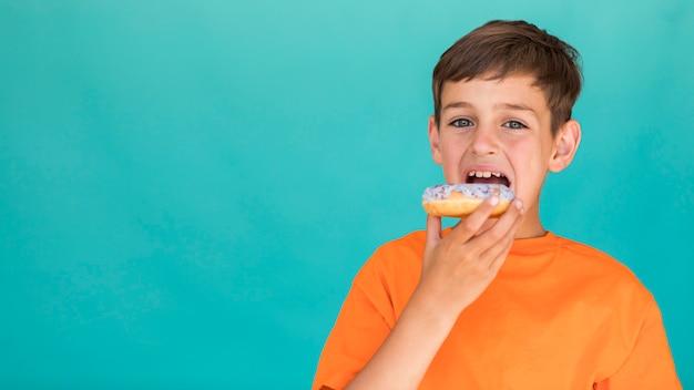 Garoto comendo um donut com espaço de cópia