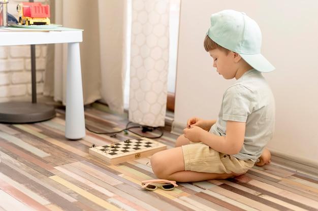 Garoto completo no chão jogando xadrez