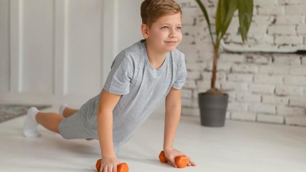 Garoto completo se exercitando dentro de casa