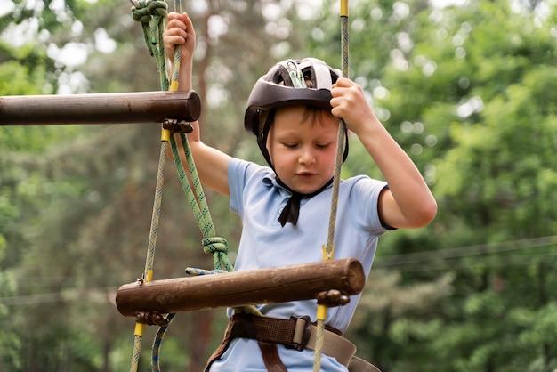 Garoto corajoso se divertindo em um parque de aventura