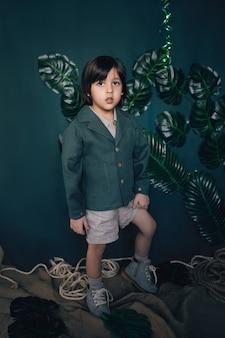 Garoto criança viajante com roupas de linho, jaqueta verde fica no estúdio