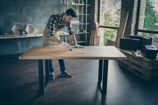 Garoto cuidadoso e bonito de corpo inteiro cobrindo laje artesanal de mesa verniz a óleo pincel própria madeira indústria de marcenaria garagem interna
