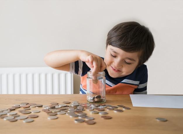 Garoto da escola colocando moedas em um pote transparente