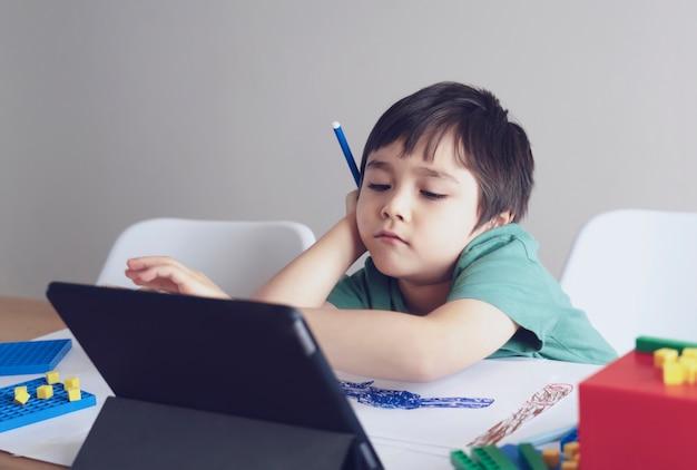 Garoto da escola em auto-isolamento usando o tablet para lição de casa, rosto triste criança deitado de cabeça para baixo olhando profundamente no pensamento, educação on-line de aprendizagem à distância social