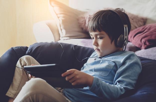 Garoto da escola usando fone de ouvido, ouvindo o professor dar aulas on-line