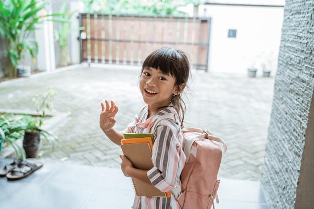 Garoto dando adeus antes de sair para a escola