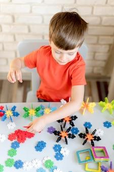 Garoto de alto ângulo com brinquedos florais