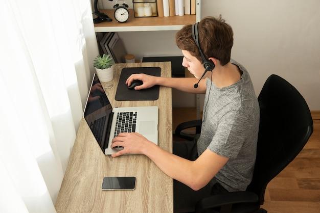 Garoto de alto ângulo jogando um jogo online com seus amigos