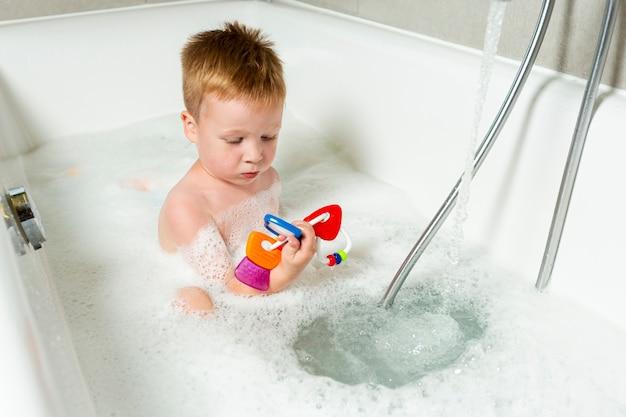 Garoto de alto ângulo na banheira com brinquedos