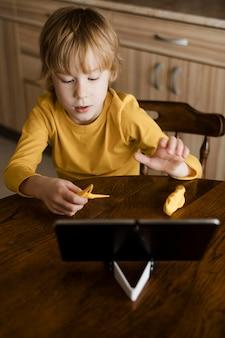 Garoto de alto ângulo usando tablet em casa