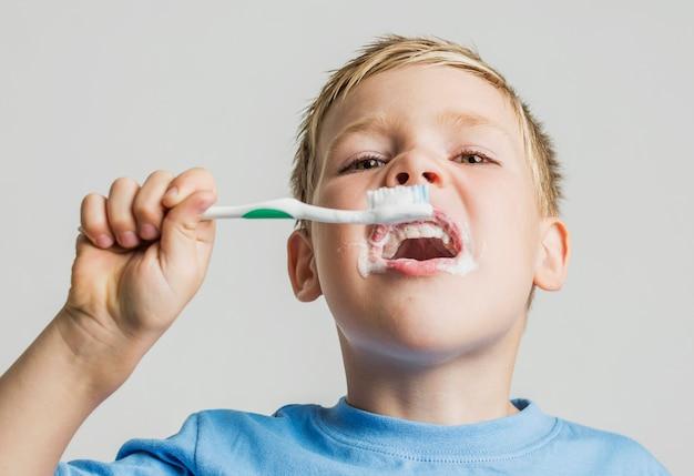 Garoto de ângulo baixo, escovando os dentes