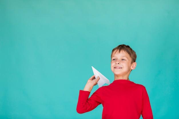 Garoto de ângulo baixo, jogando um avião de papel com espaço de cópia