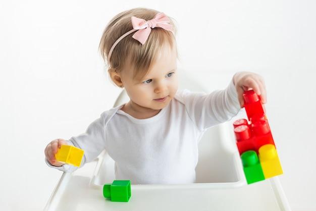Garoto de berçário brinca com brinquedos educativos em sala de aula, sentado à mesa na cadeira de bebê. menina bonitinha jogando blocos de construção coloridos. fundo branco.