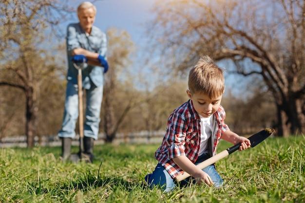 Garoto de cabelo castanho focado cuidando da natureza e trabalhando com um avô em um quintal de casa de campo