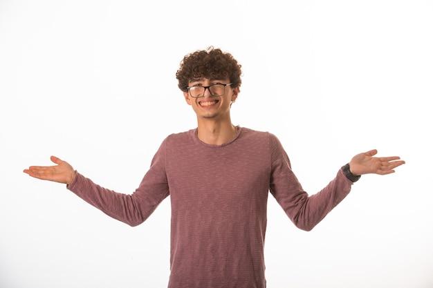 Garoto de cabelo encaracolado em óculos de óculos parece bem sucedido.