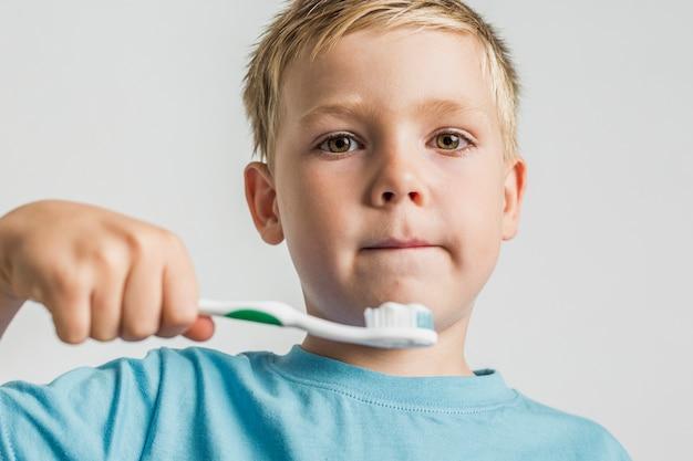 Garoto de cabelo loiro, segurando a escova de dentes
