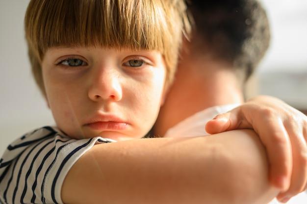 Garoto de close-up, abraçando seu pai