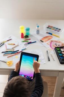 Garoto de close-up com tablet e lápis