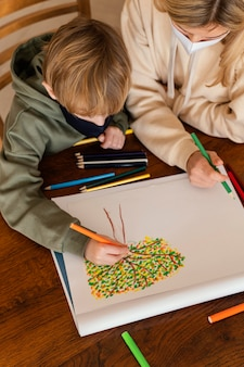 Garoto de close-up desenhando dentro de casa