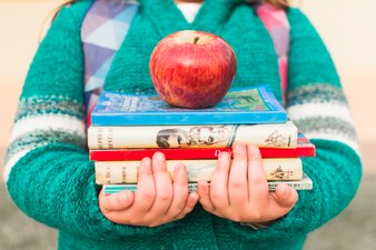 Garoto de colheita com livros e apple