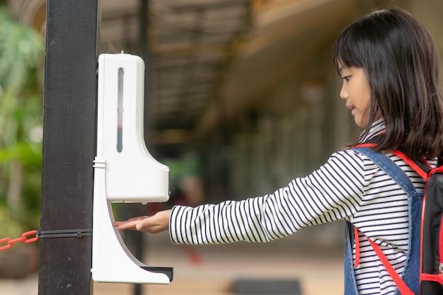 Garoto de criança usando dispensador automático de álcool gel, pulverizando na máquina desinfetante de mãos