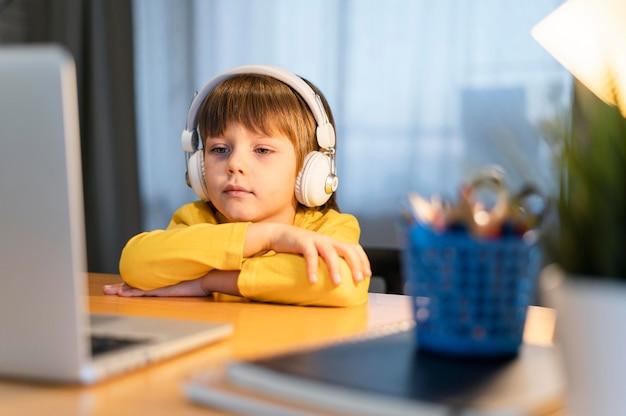 Garoto de escola com camisa amarela assistindo a uma aula virtual vista frontal
