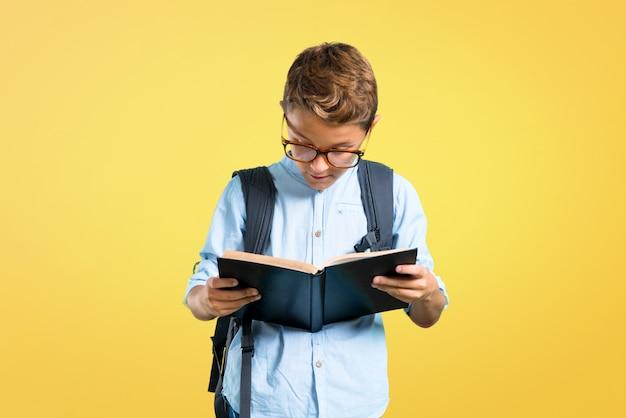 Garoto de estudante com mochila e óculos, segurando um livro sobre fundo amarelo