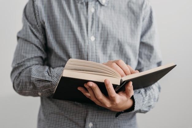 Garoto de frente lendo um livro sagrado