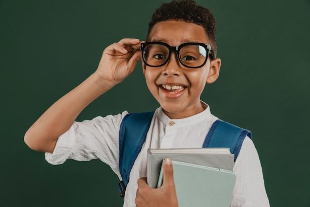 Garoto de frente organizando seus óculos de leitura