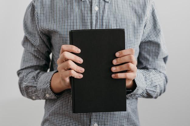 Garoto de frente segurando um livro sagrado