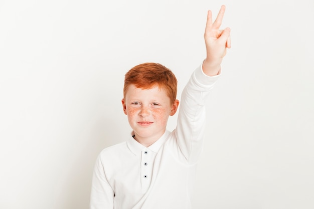Garoto de gengibre mostrando dois dedos