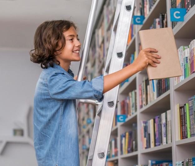Garoto de lado colocando de volta um livro na estante