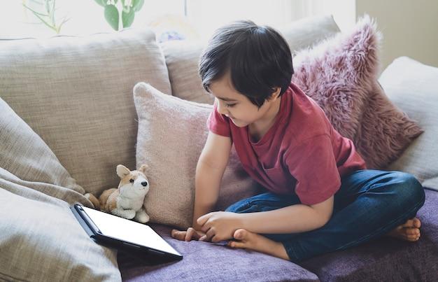 Garoto de raça mista, sentado no sofá, assistindo a desenhos animados no tablet, retrato de menino de 6-7 anos jogando no touch pad.