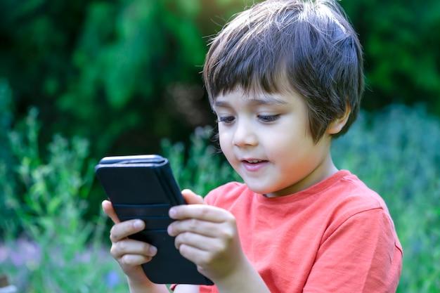 Garoto de retrato ao ar livre com um rosto feliz, jogando o jogo no celular, garoto bonito se divertindo assistindo desenhos no telefone, garoto com cara sorridente, jogando jogos.