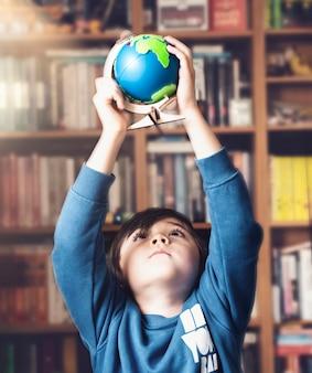 Garoto de retrato segurando o globo alto sobre a cabeça, olhando por baixo com rosto curioso, menino criança aprendendo sobre o conceito de geografia, educação e educação escolar