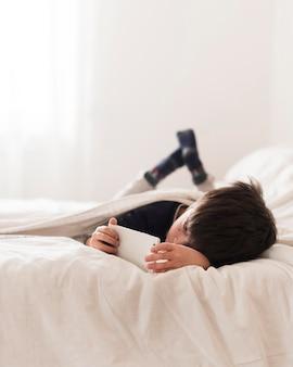 Garoto de tiro completo na cama com smartphone