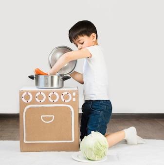Garoto de tiro completo, preparando a refeição