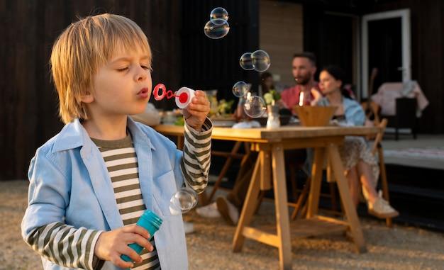 Garoto de tiro médio fazendo balões de sabão