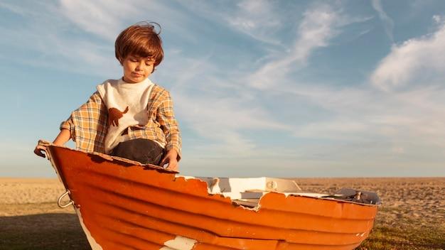 Garoto de tiro médio sentado em um barco